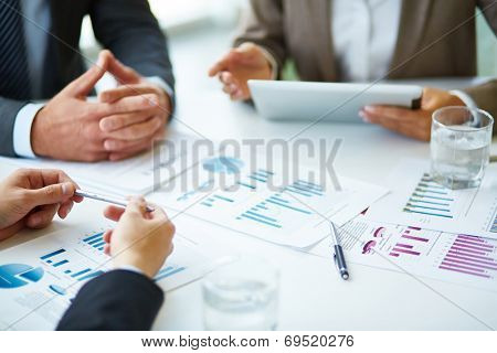Image of business documents, pen and glasses on workplace during meeting of partners