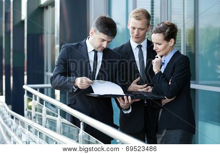 Businessman Showing Documents To His Co-workers