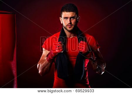 young man standing by  boxing bag in studio