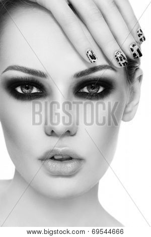 Black and white close-up portrait of young beautiful woman with stylish make-up and crackle manicure