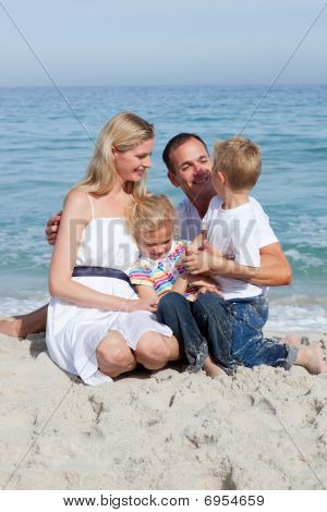 Cute Children And Their Parents Sitting On The Sand