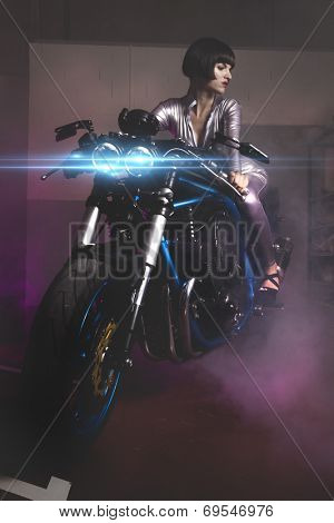 Fashion, Beautiful brunette woman wearing latex mounted on a motorcycle with a modern design