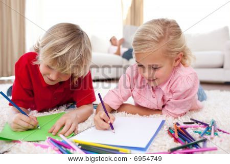 Concentrated Children Drawing Lying On The Floor