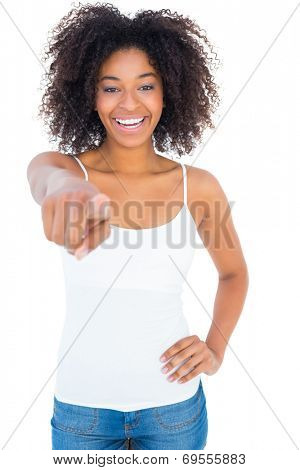 Pretty girl in white top and denim hot pants pointing at camera on white background