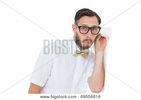 Geeky businessman eavesdropping with cup on white background