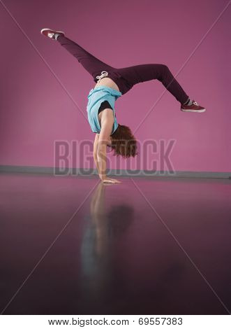 Pretty break dancer doing handstand in the dance studio