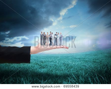 Business team looking at camera against blue sky over green field