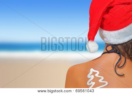 Woman on the beach in santas hat with Christmas tree shaped sunscreen