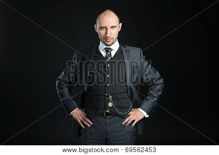 Half-length portrait of bald businessman wearing business suit