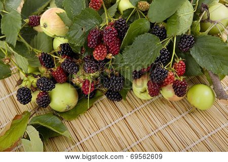 apples and raspberries on a wooden table