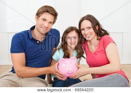 Happy Family Holding Piggy Bank At Home