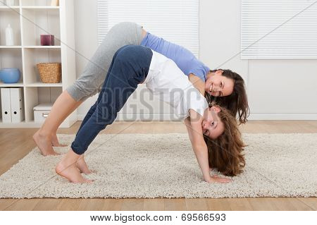 Mother And Daughter Performing Yoga At Home