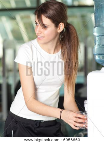 Young Woman In The Gym Drinking Water