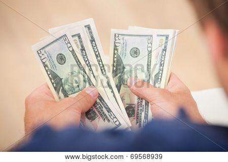 Man Counting Fifty Dollar Bills