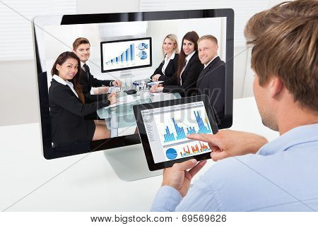Businessman Analyzing Graphs While Video Conferencing
