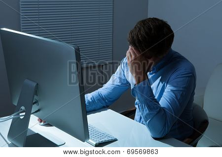 Overstressed Businessman Leaning At Computer Desk