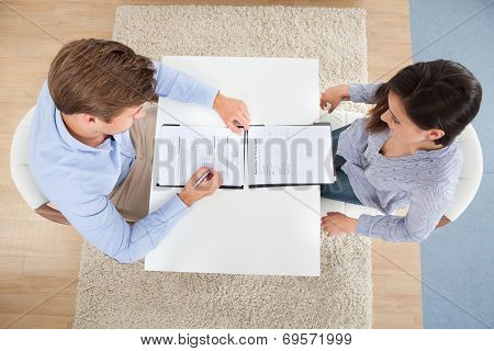 Businessman Checking Female Candidate's Resume
