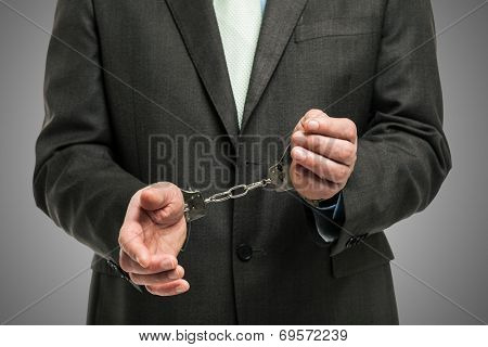 Handcuffed businessman, concept for white collar crime