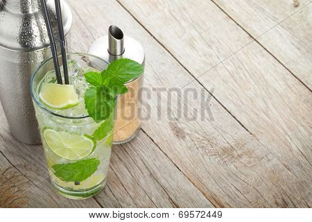 Fresh mojito cocktail and bar utensils. On wooden table with copy space