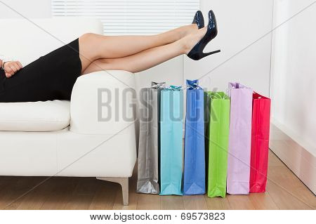 Businesswoman With Legs Over Multi Colored Shopping Bags