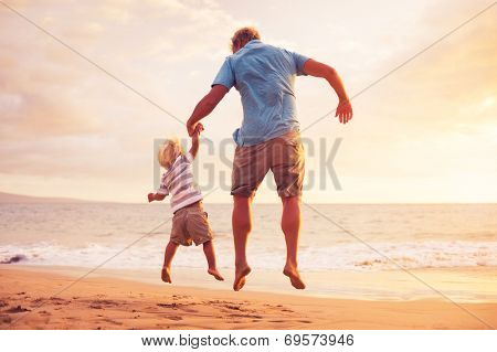 Father and son jumping for joy on the beach at sunset