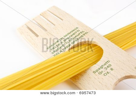 Spaghetti inside a tool that measures the servings over white background