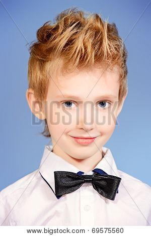 Portrait of a 7 year old boy wearing suit and bow-tie. Fashion shot.