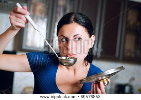 Housewife Cooks Food In Kitchen