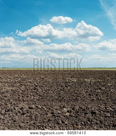 black arable field after harvesting and blue sky
