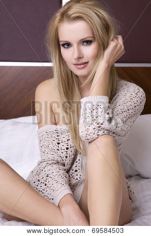 Beautiful young adult blonde woman in sweater on the bed in luxury apartment