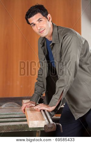 Portrait of young male carpenter cutting wood with tablesaw in workshop