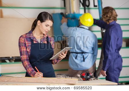 Young female carpenter holding digital tablet while coworkers working in background at workshop