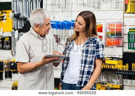 Father and daughter with digital tablet looking at each other in hardware shop