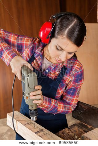 Young female carpenter using drilling machine on wood in workshop