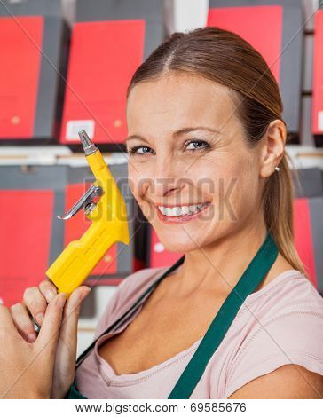 Portrait of smiling saleswoman holding air compressor hose in hardware shop