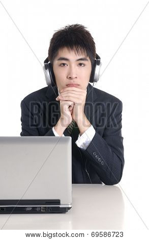 Young businessman working with headset and computer in office