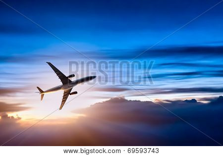 Airplane in the sky at sunrise