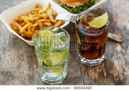 Fastfood, unhealthy. Tasty burger with fries and drink on the table