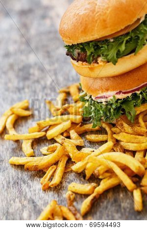 Fastfood, unhealthy. Tasty burgers with fries on the table