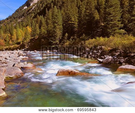 Pastoral in the Alpine mountain valley in Austria. Rapid mountain stream. Cascades of cold water at the source of the famous Krimml waterfalls.
