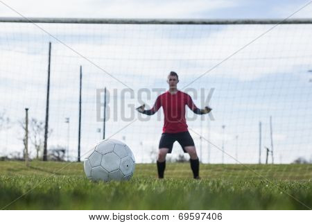 Goalkeeper in red ready to make a save on a clear day