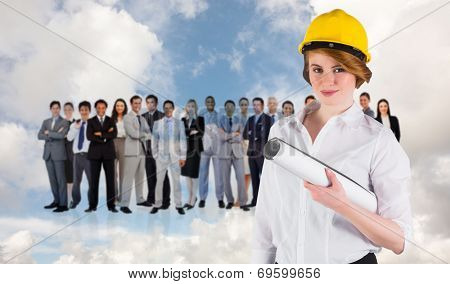 Pretty young architect smiling at camera against blue sky with white clouds and business people