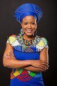 pic of zulu  - smiling young zulu woman with arm crossed on black background - JPG
