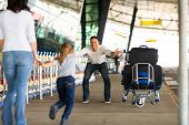 stock photo of excite  - excited little girl running to her father at airport after a long wait with mother - JPG