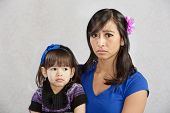 picture of disappointed  - Disappointed Asian mother holding serious female toddler - JPG