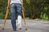 picture of crutch  - Young Asian man on crutches with tree background - JPG