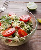 stock photo of tabouleh  - Tabbouleh with couscous and parsley healthy salad in glass bowl on wooden table - JPG