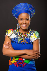 picture of zulu  - smiling young zulu woman with arm crossed on black background - JPG