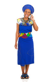 stock photo of zulu  - full length portrait of african zulu woman talking on mobile phone - JPG