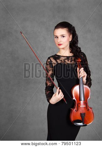 Portrait Of A Young Attractive Violinist Woman In A Black Evening Dress